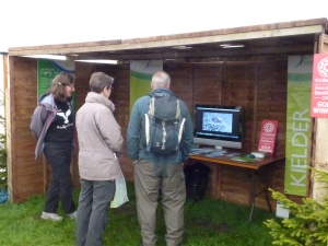 A couple of the visitors watch the video loop, with Sally as their guide (c) Joanna Dailey